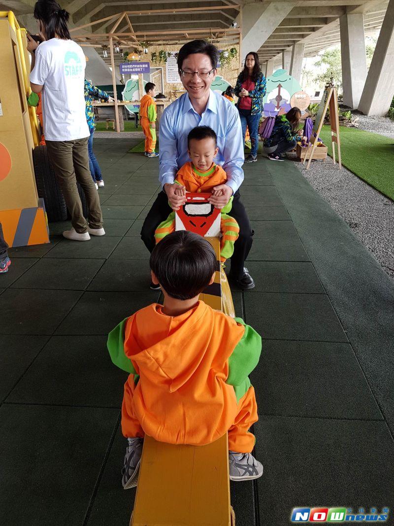 ▲環保局長周錫福與小朋友玩以再生材質做成的蹺蹺板。(圖/記者李清貴攝,2017.3.30)