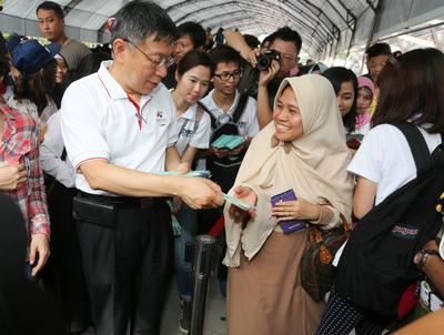 台北市政府主辦開齋節活動,25日在行旅廣場熱鬧登場,市長柯文哲(前左)到場贈送限量特製的綠色「紅包」和穆斯林朋友們一同歡慶這個大日子。中央社記者謝佳璋攝 106年6月25日