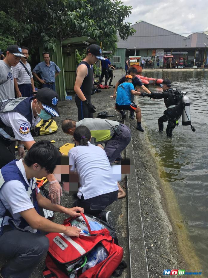 一名男子疑似酒醉失足落水,消防人員將他拉上岸後,準備就醫。(圖/記者宋德威攝 , 2017.08.14)