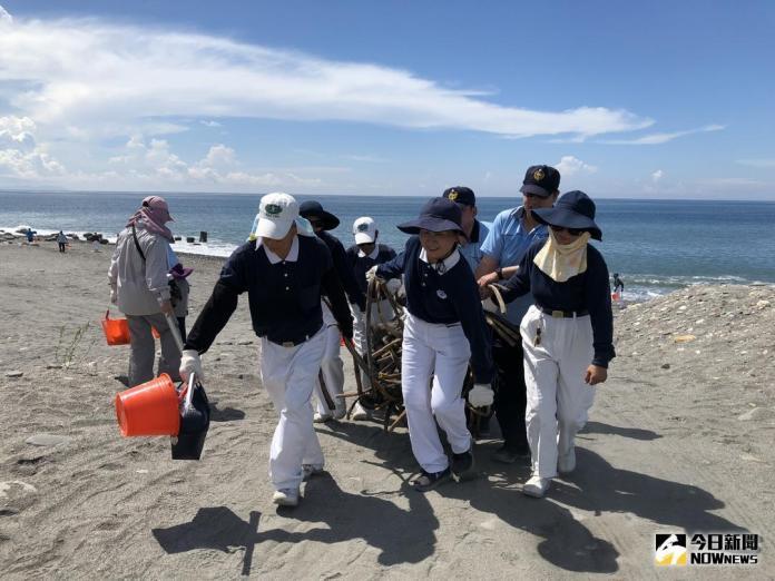 ▲慈濟志工與海巡署弟兄一起搬運著纏繞水管的巨大廢棄物,將之從沙灘拖上岸。(圖/慈濟基金會提供)