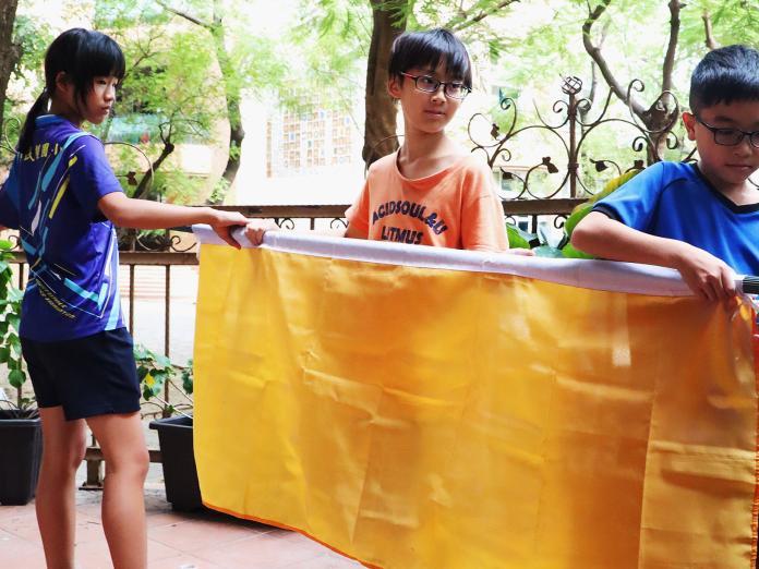 ▲學生們依據AQI(空氣品質指標)於每日8時及12時30更換空品旗。(圖/高市教育局提供)