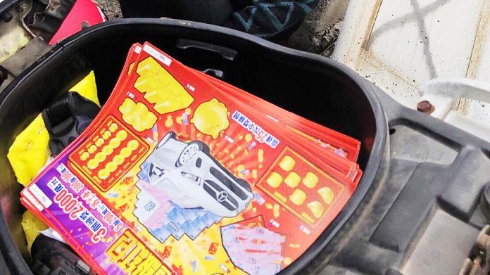 ▲警方在吳男的機車置物箱內查獲34張刮刮樂彩券。(圖/高市警局提供)