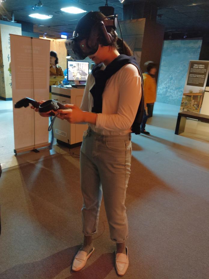 只要戴上頭盔與裝置,民眾即可透過VR虛擬實境體驗書畫世界。(圖/國立故宮博物院提供)