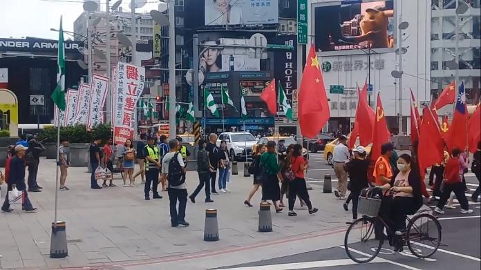 ▲一群人舉旗穿越馬路繞行,並與台獨旗隊擦肩而過。(圖/西門町台獨旗隊提供)