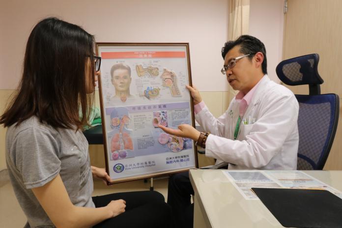亞大醫院胸腔內科主任黃建文向患者講解氣喘致病原因。(圖非當事人)