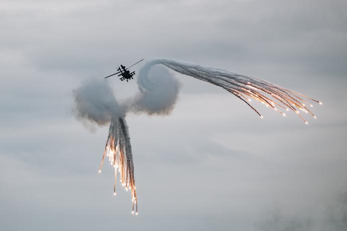 ▲AH-64E阿帕契攻擊直升機先制攻擊摧毀目標後,施放熱焰彈脫離戰場。(圖/軍聞社提供)