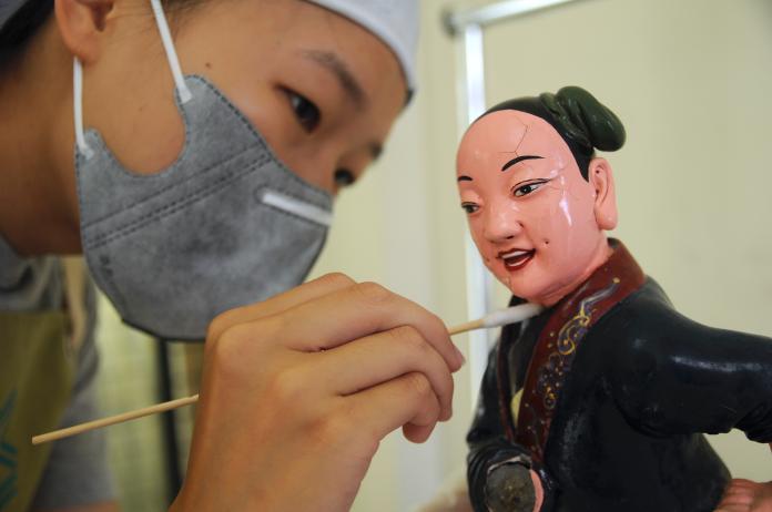 周志明的團隊在修復神像前,利用棉花棒簡單清潔神像的外層,不正確的清潔方式可能造成神像的損壞。 (初聲/周志明提供)
