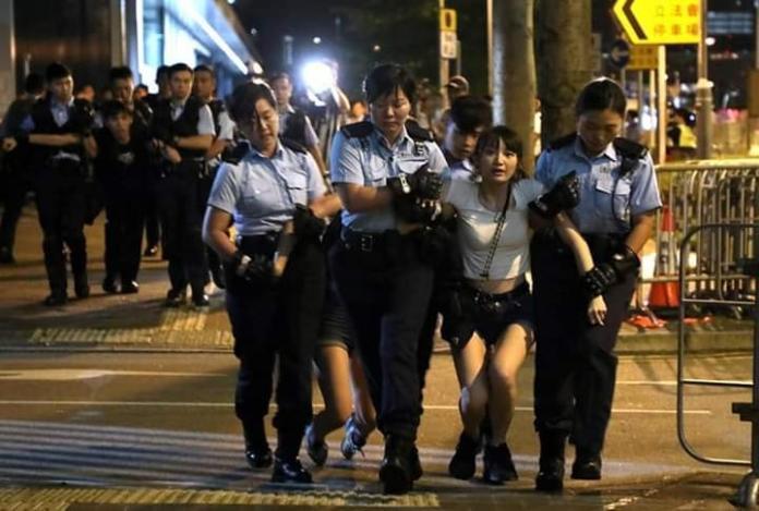 ▲有網友在一堆的示威民眾的相片之中,發現了一位被香港武警架離的「胸狠熱褲妹」。(圖/翻攝自爆廢公社)
