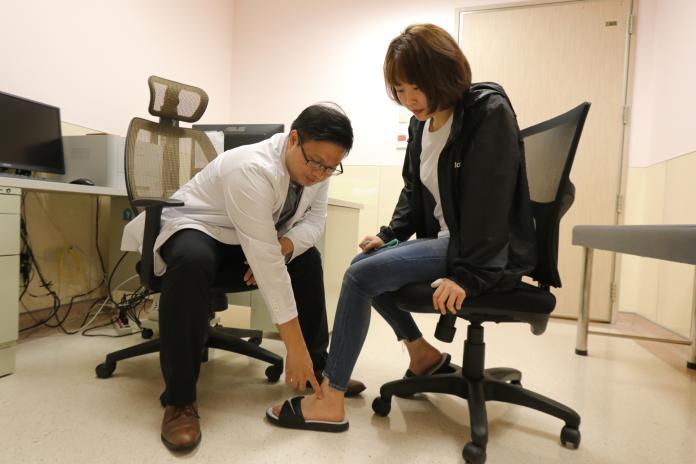 ▲亞大醫院腹膜透析主任林軒任替患者檢查腳踝浮腫情形(圖非當事人)。(圖/亞大附屬醫院提供)