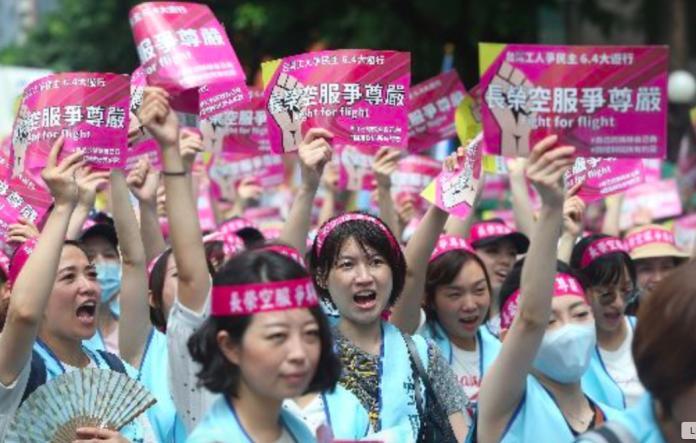 ▲長榮空服員發動罷工,身穿藍背心、頭繫粉色布條,要求資方聽見勞方聲音。(圖/中央社)