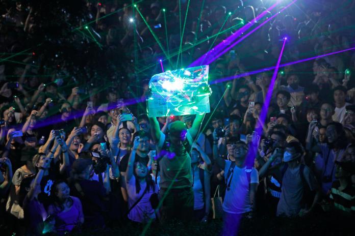 ▲不服警方以雷射筆有危險性為由逮人,有香港人在「觀星」聲援活動中以雷射筆投射在報紙上,結果並未起火。(圖/美聯社/達志影像)
