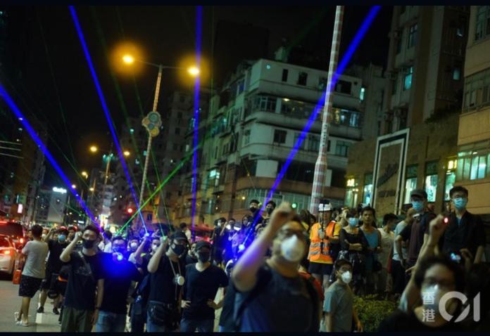 ▲示威者拿著雷射筆射向警署。(圖/翻攝香港01)