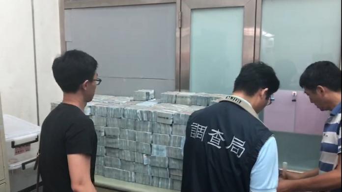 調查幹員查扣現金,忙著數錢。