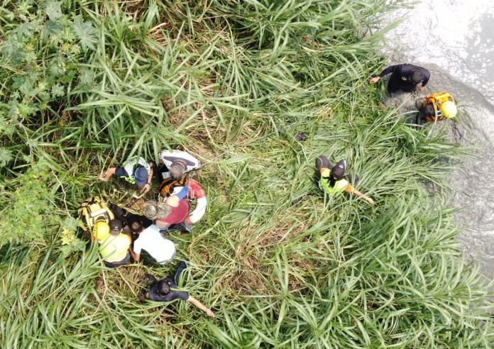 <br> ▲釣客受困在溪水湍急的消波塊,消防人員冒險涉水救人。(圖/雲林縣消防局提供)