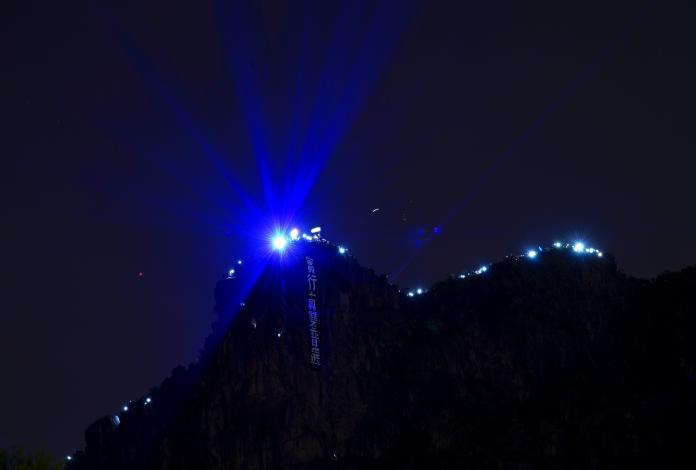 <br> ▲ 13 日晚上有香港民眾登上著名的獅子山頂,以鐳射光、手機螢幕光等照耀,甚至懸掛出「實行真雙普選」的訴求旗幟。(圖/美聯社/達志影像)