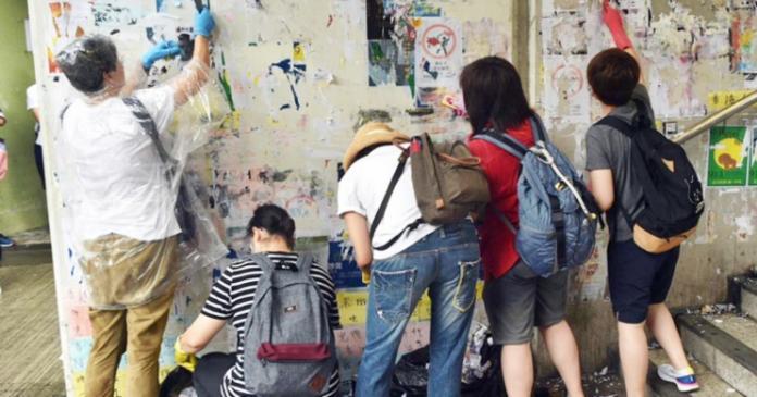 ▲近10名香港市民到港鐵長沙灣站外清理由反對修訂《逃犯條例》人士張貼的「連儂牆」。(圖/翻攝巴士的報)