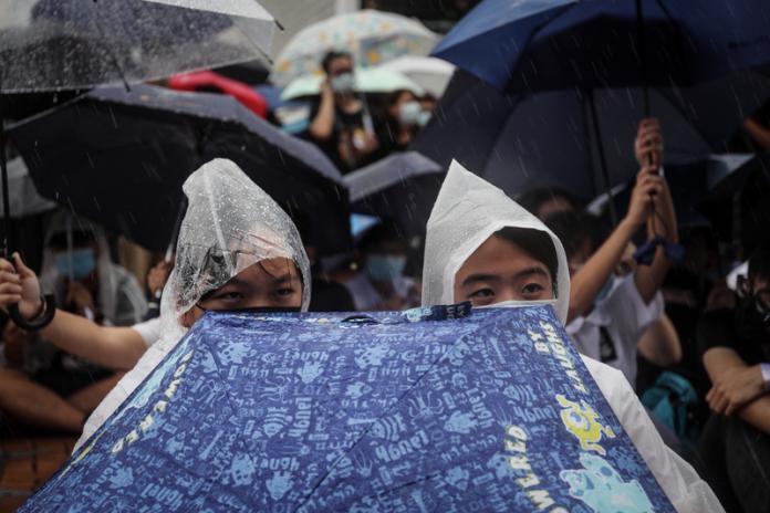 ▲香港反送中延燒,中學生2日在中環愛丁堡廣場發起罷課集會,要求港府回應反條例「5大訴求」,儘管雨越下越大,仍澆不熄學生熱情。中央社記者吳家昇攝108年9月2日