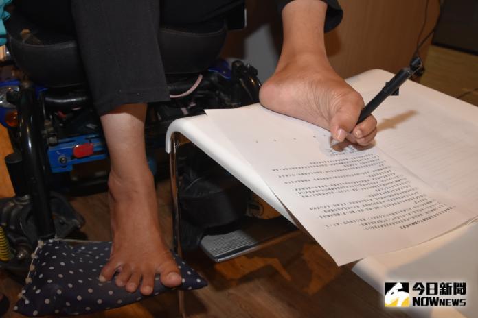 <br> ▲秀秀用腳趾夾筆簽名。(圖/記者陳雅芳攝,2019.10.03)