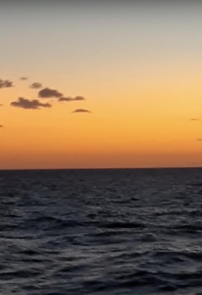 ▲在夕陽西下的同時,海峽的另一端竟出現了「大量的不明發光體」。(圖/翻攝自影片)