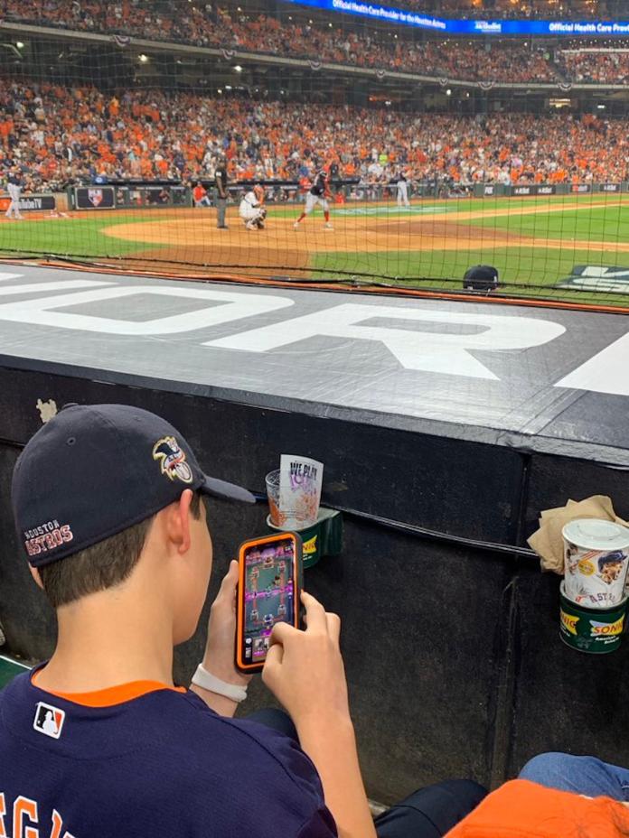 ▲小球迷在世界大賽現場玩手機遊戲,引起熱議。(圖/取自 Darren Rovell 推特)