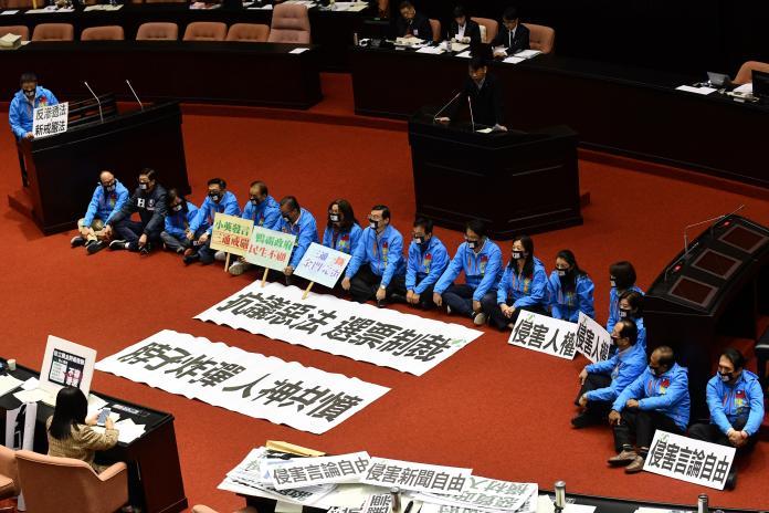 國民黨團立委為了抗議民進黨倉促通過反滲透法,將抗議標語鋪在議場上,並直接席地而坐戴上黑色口罩,表達無聲抗議。