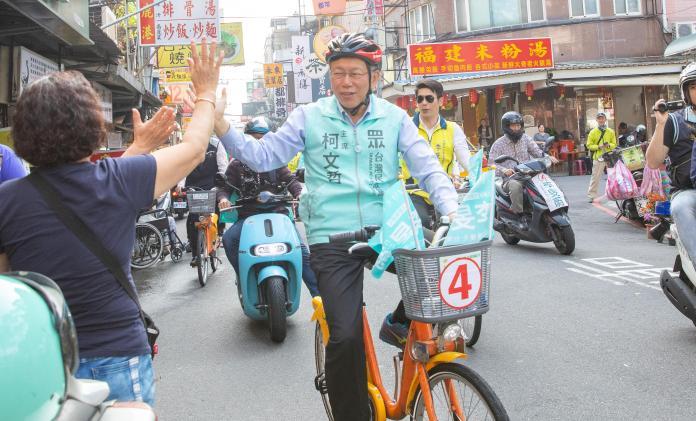 身兼台灣民眾黨主席的台北市長柯文哲,騎腳踏車為民眾黨三重立委候選人李旻蔚掃街拜票。