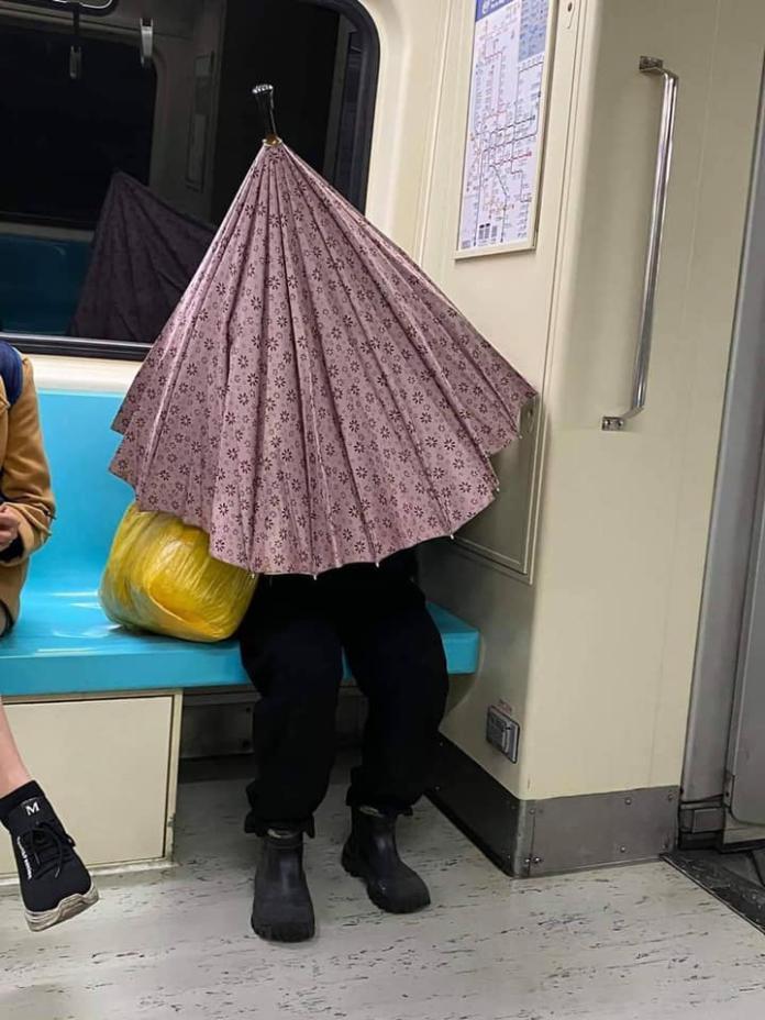 <br> ▲照片中一位民眾在捷運車廂內打傘。(圖/FB/meanwhileintaiwan)