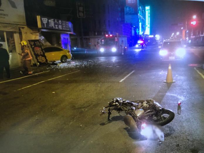 遭高速衝撞,機車嚴重扭曲變形,零件四處飛散,計程車失控撞入一旁店家