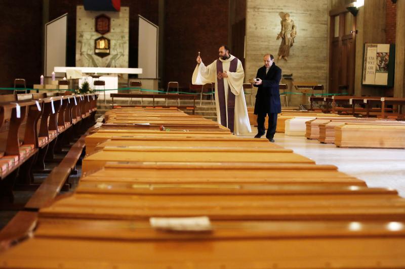 ▲義大利神父為因新冠肺炎死去的人們祈禱。(圖/美聯社/達志影像)