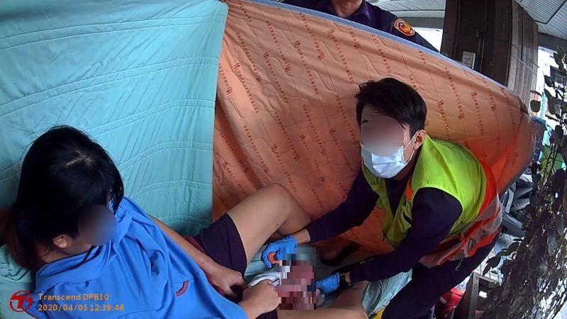 ▲警消緊急在騎樓下用棉被圍成產房,臨時為孕婦接生。(圖/ 警方提供 )