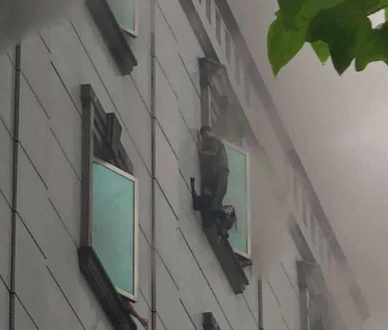 ▲林森北錢櫃火災,受困民眾爬出窗外等待救援。(圖/可蜜達comida林森店提供)