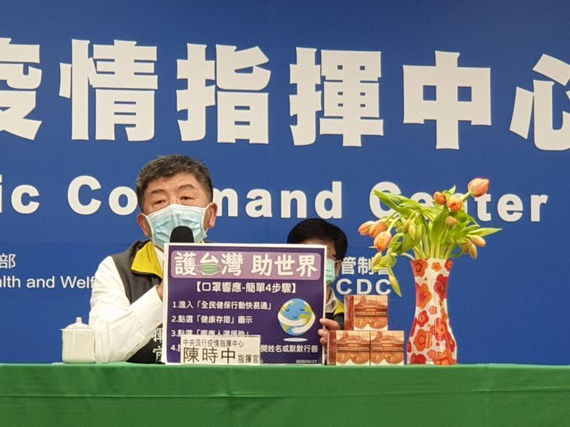 ▲指揮中心指揮官陳時中舉起「護台灣、助世界」標語,來響應口罩人道援助。(圖/記者許家禎攝)