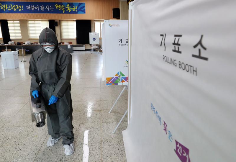 ▲韓國大選投票日的消毒人員。(圖/翻攝自《中央日報》)