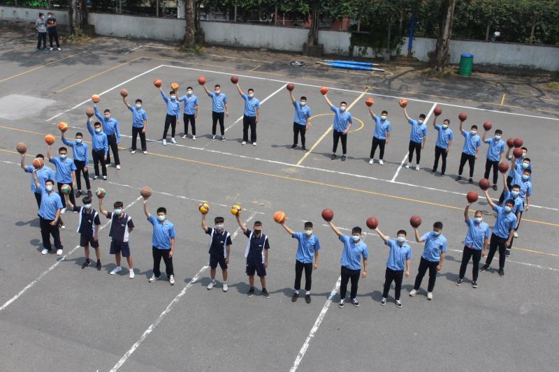 ▲排球及籃球校隊員在下操場,手舉籃、排球形成「零」圈,期許著永遠「零」確診。(圖/竹林中學提供)
