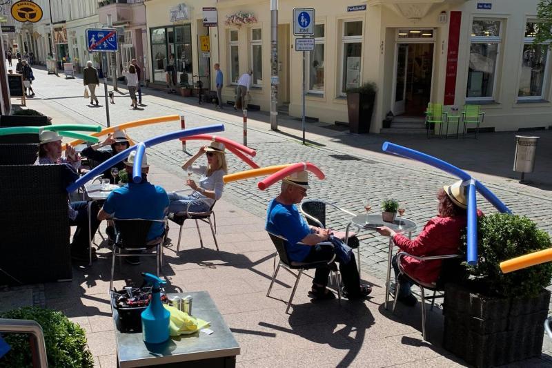 ▲德國施威林一家咖啡館為了保持社交距離,要求顧客戴上特製的游泳浮條帽。(圖/翻攝Cafe & Konditorei Rothe臉書)