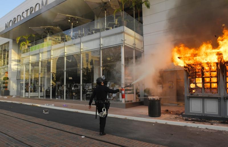 ▲警察在店家外滅火。(圖/美聯社/達志影像)