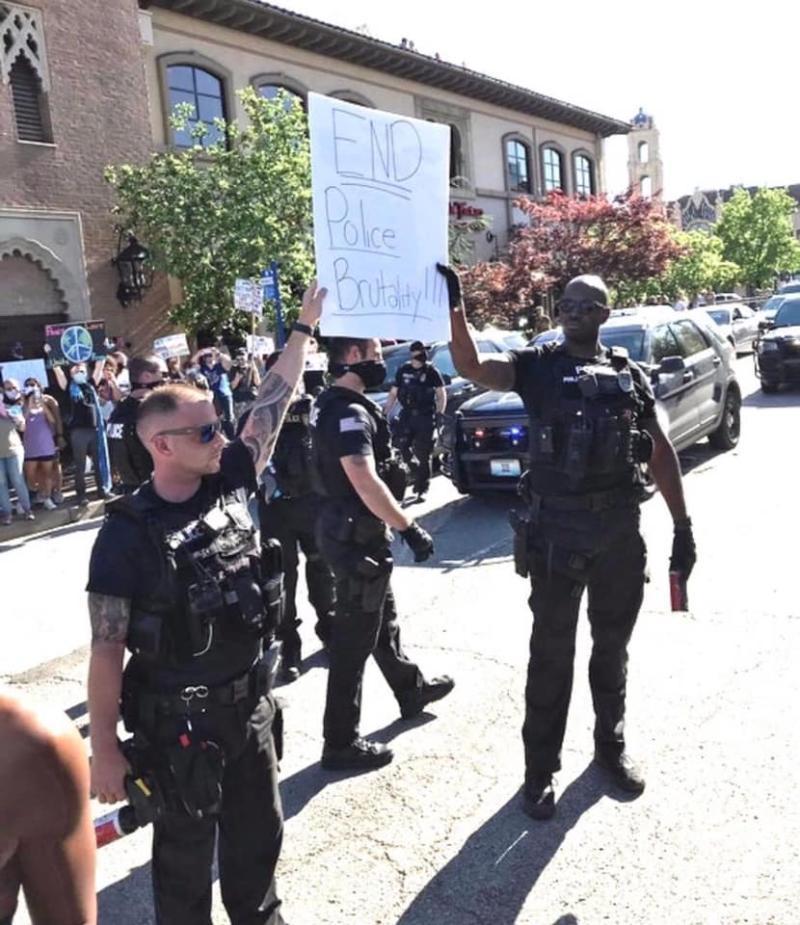 ▲有美國警員加入抗議陣營,高舉「停止警暴」標語。(圖/翻攝自《杜汶澤