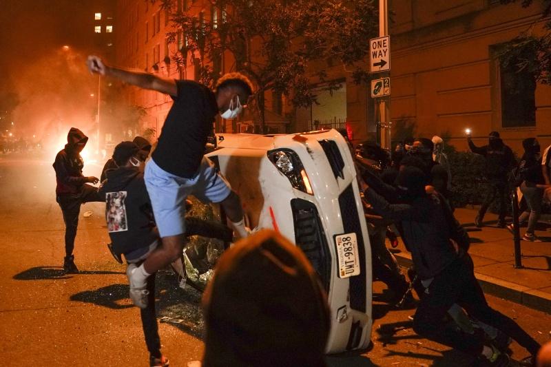 ▲憤怒的示威者將汽車推倒並打砸。(圖/美聯社/達志影像)