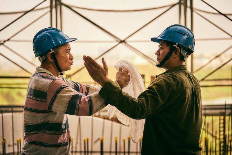 ▲李銘順(左)與柯叔元劇中兩兄弟,在工地即興搬演布袋戲人物「素還真」過招。(圖