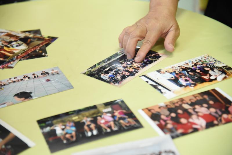 ▲關愛之家創辦人楊姊,拿出歷年來照顧愛滋病友、帶他們出去玩的照片。(圖/記者陳明安拍攝)