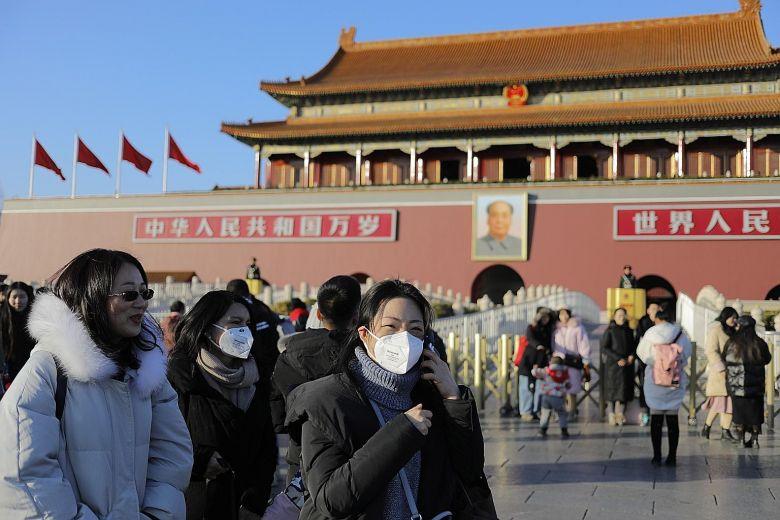 ▲今年年初爆發 COVID-19 第一波疫情時,在北京配戴口罩的民眾。(圖/翻攝自《海峽時報》)