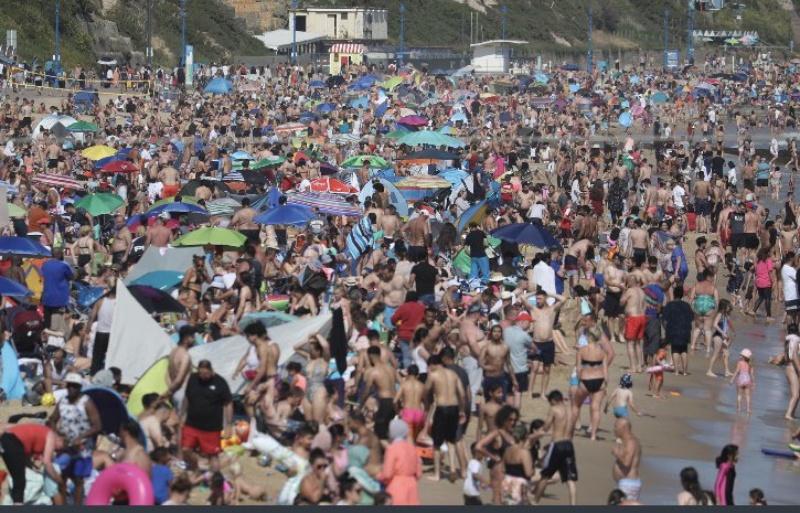 ▲英國伯恩茅斯多塞特郡的海灘,近日一口氣湧入 50 萬名民眾戲水消暑,造成許多亂象和防疫隱憂。(圖/翻攝自 Tobias Ellwood MP 推特)