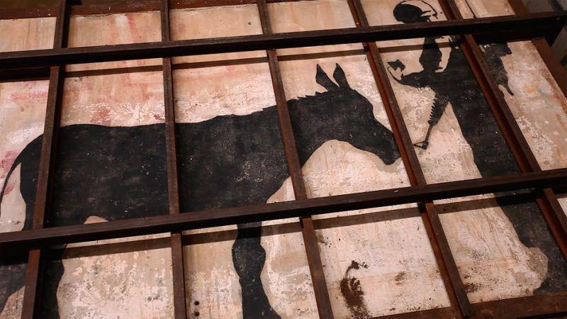 ▲▼一頭驢子向以色列軍官出示通行證,是班克西的大作。(圖/車庫)