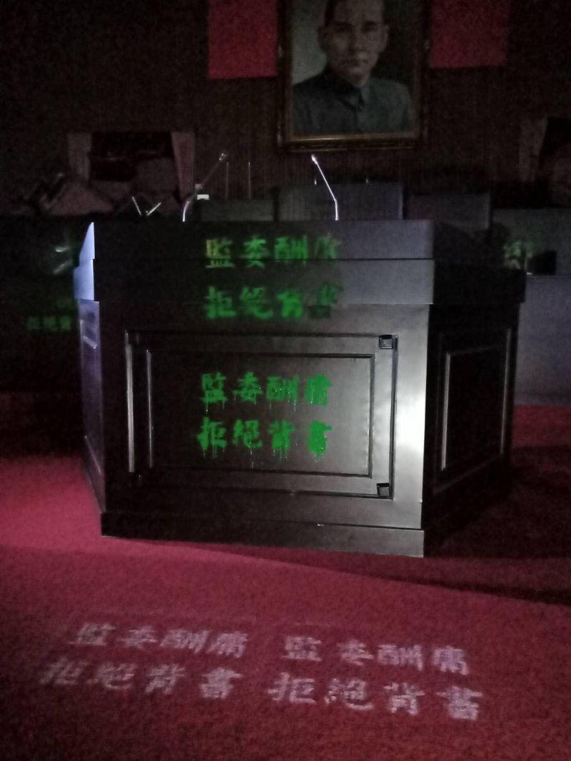 ▲破壞議場大門後,國民黨立委在發言台及主席台上,以綠色噴漆噴上「監委酬庸、拒絕背書」等字樣。(圖/立委洪孟楷辦公室提供)