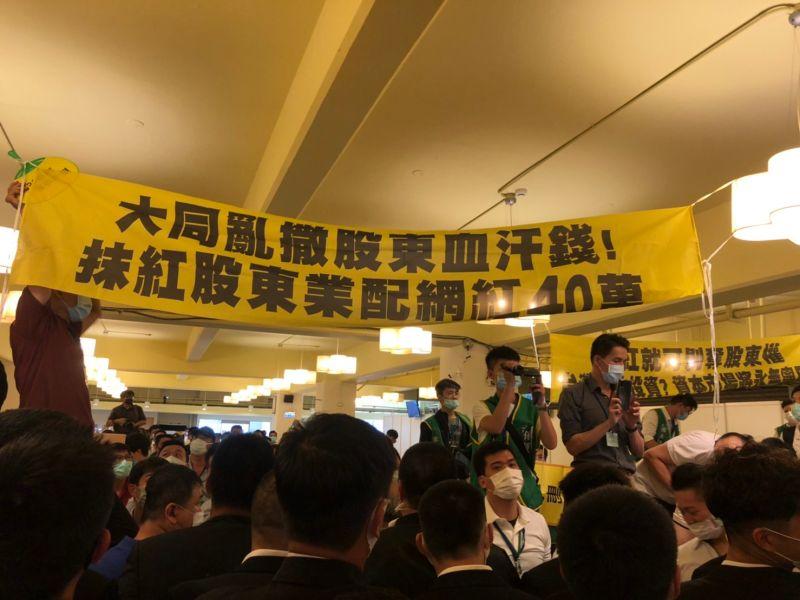 ▲大同股東會今(30)日登場,場內股東們舉起布條抗議。(圖/讀者提供)