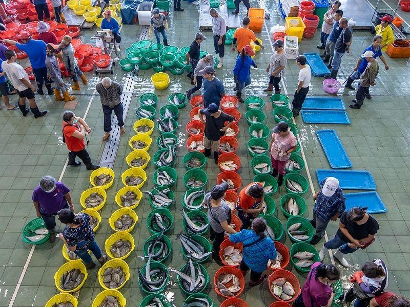 ▲高雄蚵仔寮漁港生鮮魚貨拍賣市場,採買漁貨人潮爆滿。(資料照/記者黃守作攝)