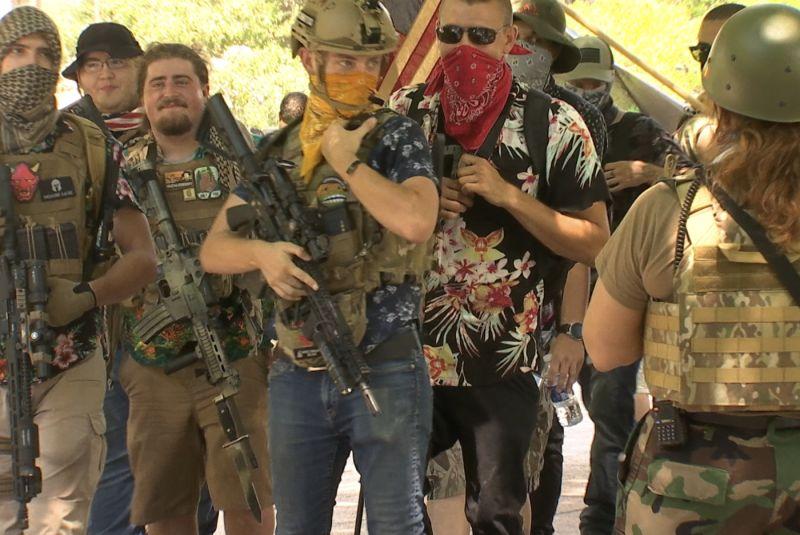 ▲持槍人士保護反對戴口罩的示威者。(圖/翻攝自The
