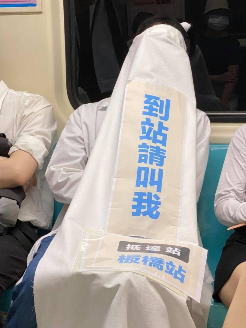 ▲有乘客搭捷運怕睡過頭,在身上蓋醒目布條求提醒,引發熱議。(圖/翻攝自台灣迷因