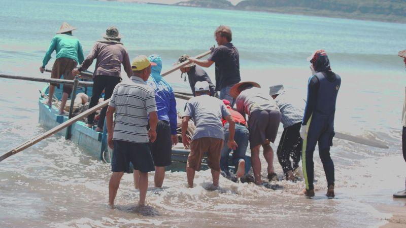 ▲另項古老傳統捕魚方式為牽罟文化,划著舢舨的漁民,先將曳地網撒到海裡,再由岸上的人協力拖行魚網上岸。(圖/新北市文化局提供)