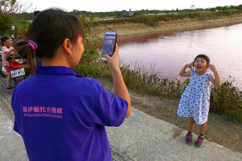 ▲超夢幻的粉紅色漁塘,勾起不少民眾少女心,專程跑到現場拍照打卡。(圖/記者蔡若喬攝)